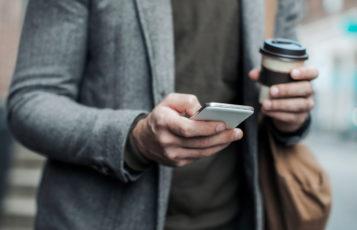 Man med mobil och kaffemugg